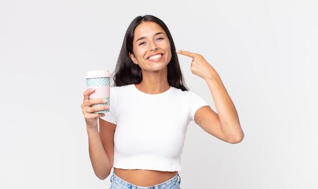 Jonge spaanse vrouw die vol vertrouwen glimlacht, wijst naar haar eigen brede glimlach en houdt een afhaalkoffiecontainer vast