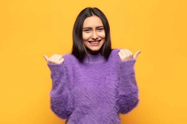 Jonge spaanse vrouw die vreugdevol glimlacht en er gelukkig uitziet, zich zorgeloos en positief voelt met beide duimen omhoog