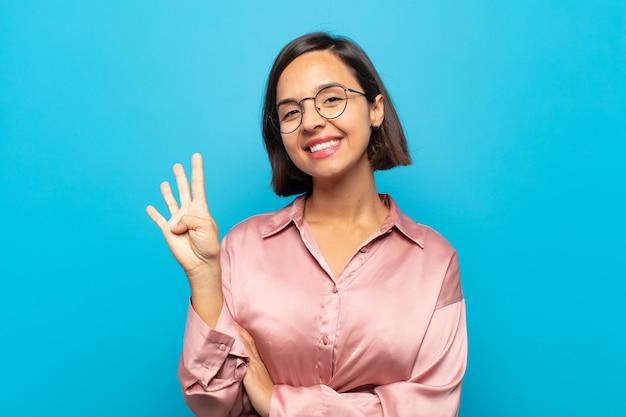 Jonge spaanse vrouw die vriendelijk glimlacht en kijkt, nummer vier of vierde met vooruit hand toont, aftellend