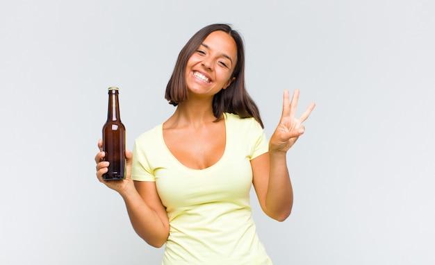 Jonge spaanse vrouw die vriendelijk glimlacht kijkt, nummer één toont of eerst met vooruit hand, aftellend