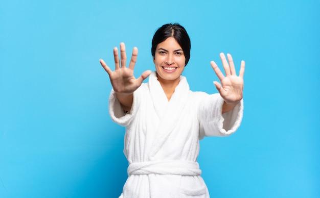 Jonge spaanse vrouw die vriendelijk glimlacht kijkt, nummer tien of tiende met vooruit hand toont, aftellend. badjas concept