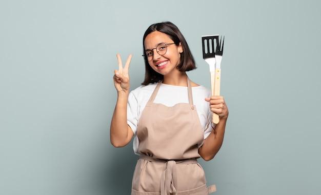 Jonge spaanse vrouw die vriendelijk glimlacht kijkt, nummer twee of seconde met vooruit hand toont, aftellend