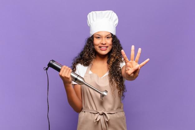 Jonge spaanse vrouw die vriendelijk glimlacht kijkt, nummer vier of vierde met vooruit hand toont, aftellend. chef-kok concept