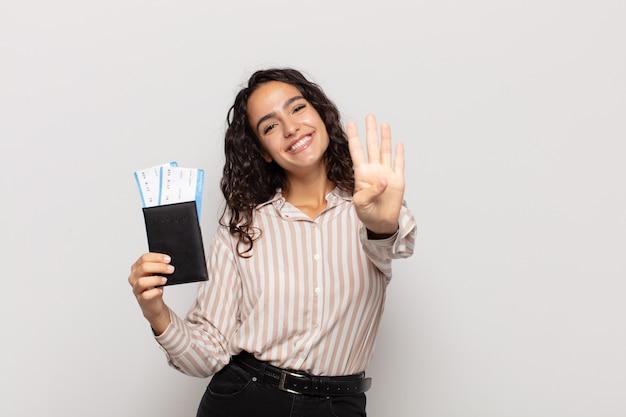 Jonge spaanse vrouw die vriendelijk glimlacht kijkt, nummer vier of vierde met vooruit hand toont, aftellend