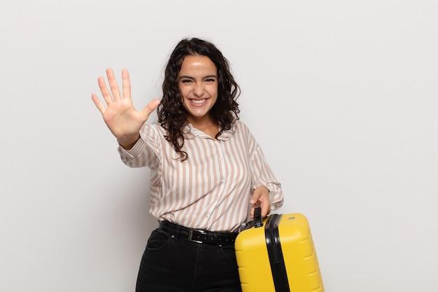 Jonge spaanse vrouw die vriendelijk glimlacht kijkt, nummer vijf of vijfde met vooruit hand toont, aftellend