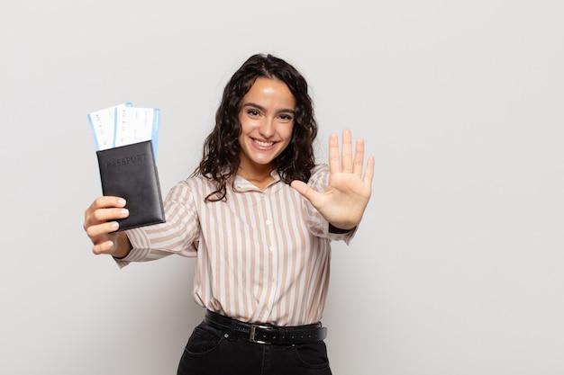 Jonge spaanse vrouw die vriendelijk glimlacht kijkt, nummer vijf of vijfde met vooruit hand toont