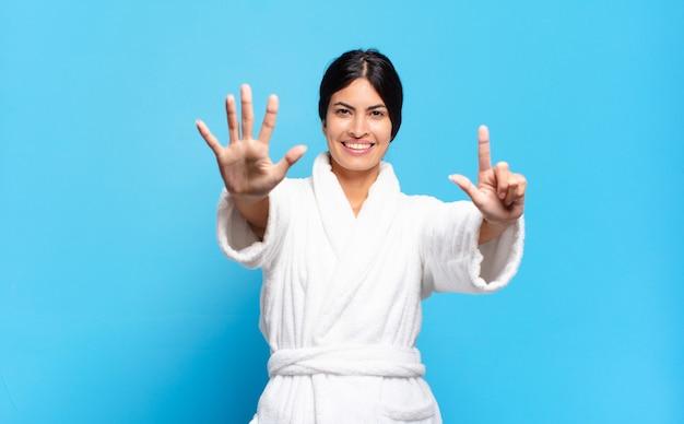 Jonge spaanse vrouw die vriendelijk glimlacht kijkt, nummer zeven of zevende met vooruit hand toont, aftellend. badjas concept