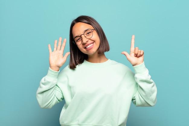 Jonge spaanse vrouw die vriendelijk glimlacht kijkt, nummer zeven of zevende met vooruit hand toont, aftellend