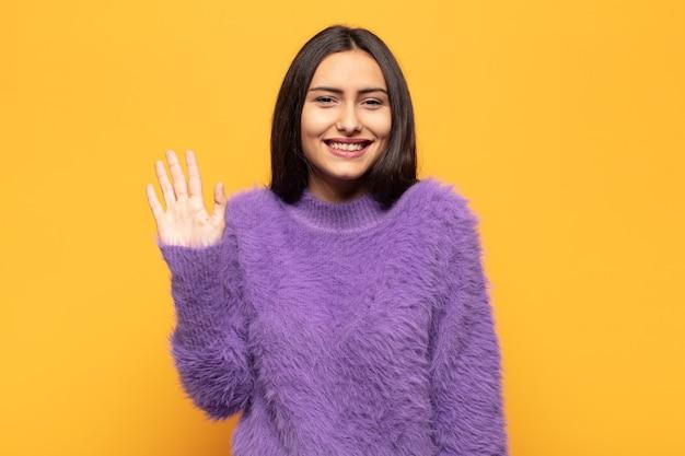 Jonge spaanse vrouw die vrolijk en opgewekt lacht, met de hand zwaait, je verwelkomt en begroet, of afscheid neemt