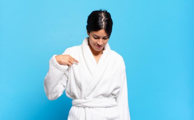 Jonge spaanse vrouw die vrolijk en terloops glimlacht, naar beneden kijkt en naar de borst wijst. badjas concept