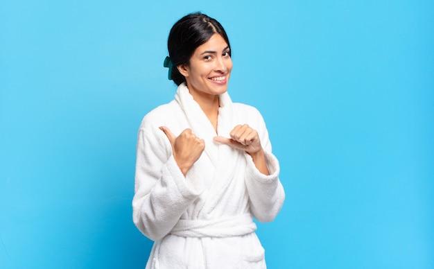 Jonge spaanse vrouw die vrolijk en terloops glimlacht wijzend om ruimte aan de kant te kopiëren, zich gelukkig en tevreden voelt. badjas concept