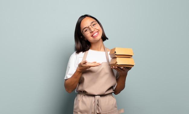 Jonge spaanse vrouw die vrolijk glimlacht, zich gelukkig voelt en een concept in exemplaarruimte met handpalm toont
