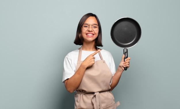 Jonge spaanse vrouw die vrolijk glimlacht, zich gelukkig voelt en naar de zijkant en omhoog wijst, voorwerp in exemplaarruimte toont
