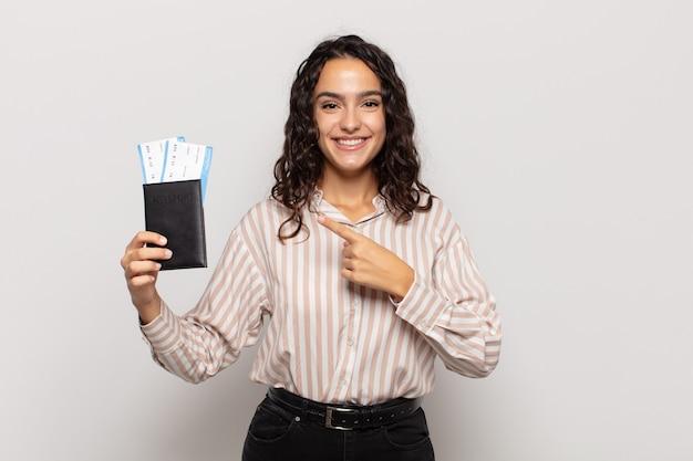 Jonge spaanse vrouw die vrolijk glimlacht, zich gelukkig voelt en naar opzij en omhoog wijst, voorwerp in exemplaarruimte toont