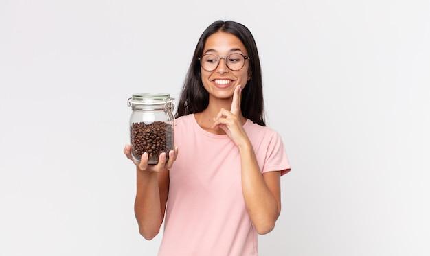 Jonge spaanse vrouw die vrolijk lacht en dagdroomt of twijfelt en een fles koffiebonen vasthoudt