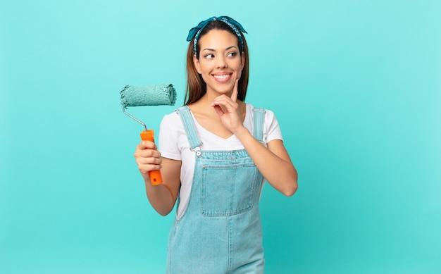 Jonge spaanse vrouw die vrolijk lacht en dagdroomt of twijfelt en een muur schildert