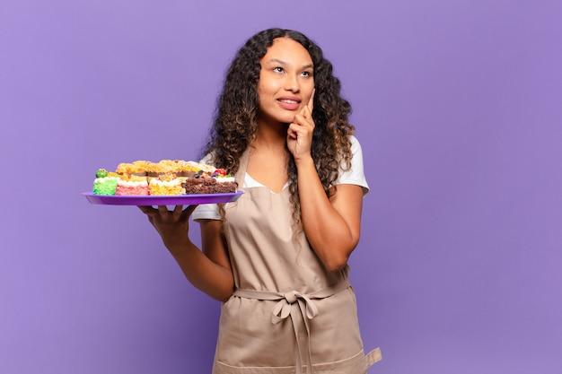 Jonge spaanse vrouw die vrolijk lacht en dagdroomt of twijfelt, opzij kijkend. koken taarten concept