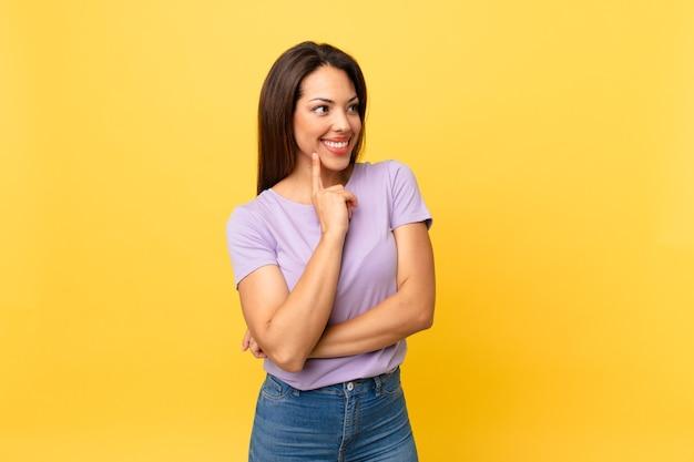 Jonge spaanse vrouw die vrolijk lacht en dagdroomt of twijfelt
