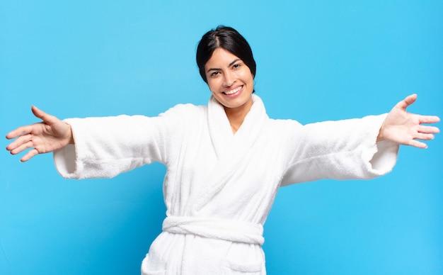 Jonge spaanse vrouw die vrolijk lacht en een warme, vriendelijke, liefdevolle welkomstknuffel geeft, zich gelukkig en schattig voelt. badjas concept