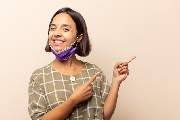 Jonge spaanse vrouw die vrolijk lacht en wijst naar een medisch masker opzij