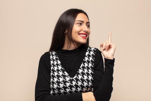 Jonge spaanse vrouw die vrolijk lacht en zijwaarts kijkt, zich afvraagt, denkt of een idee heeft
