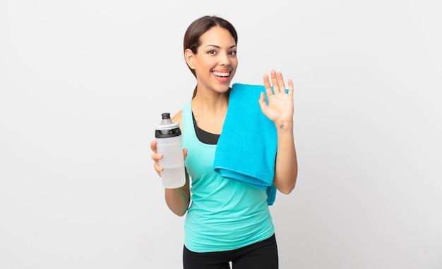 Jonge spaanse vrouw die vrolijk lacht, met de hand zwaait, je verwelkomt en begroet. fitnessconcept