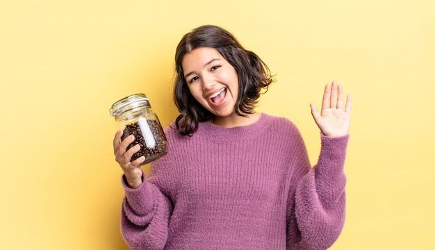 Jonge spaanse vrouw die vrolijk lacht, met de hand zwaait, je verwelkomt en begroet. koffiebonen concept