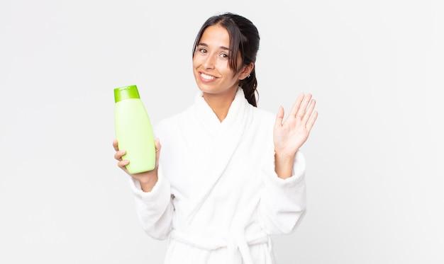 Jonge spaanse vrouw die vrolijk lacht, met de hand zwaait, je verwelkomt en begroet met een badjas en een shampoo vasthoudt