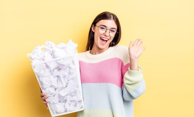 Jonge spaanse vrouw die vrolijk lacht, met de hand zwaait, je verwelkomt en begroet. mislukking prullenbak concept