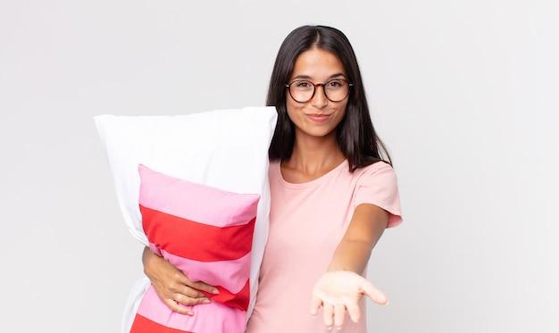 Jonge spaanse vrouw die vrolijk lacht met vriendelijk en een concept aanbiedt en toont dat een pyjama draagt en een kussen vasthoudt