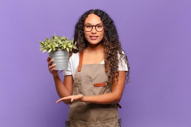 Jonge spaanse vrouw die vrolijk lacht, zich gelukkig voelt en een concept in kopieerruimte toont met handpalm
