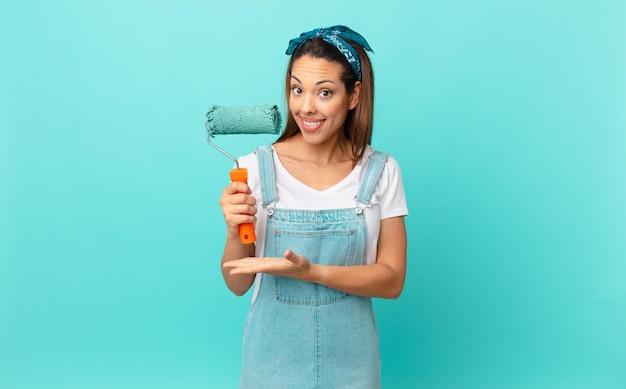 Jonge spaanse vrouw die vrolijk lacht, zich gelukkig voelt en een concept laat zien en een muur schildert