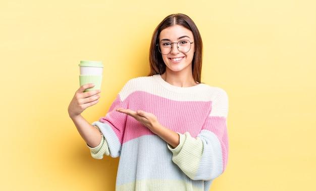 Jonge spaanse vrouw die vrolijk lacht, zich gelukkig voelt en een concept toont. afhaal koffie concept