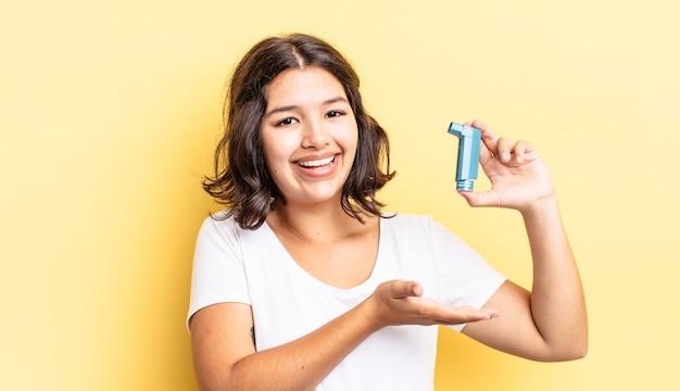 Jonge spaanse vrouw die vrolijk lacht, zich gelukkig voelt en een concept toont. astma concept