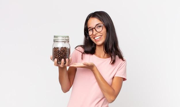 Jonge spaanse vrouw die vrolijk lacht, zich gelukkig voelt en een concept toont en een fles koffiebonen vasthoudt
