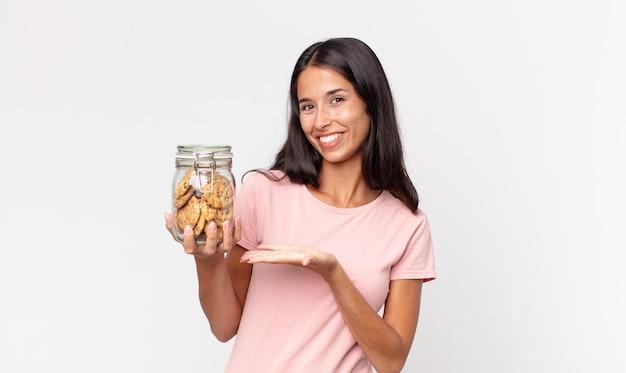 Jonge spaanse vrouw die vrolijk lacht, zich gelukkig voelt en een concept toont en een glazen fles met koekjes vasthoudt