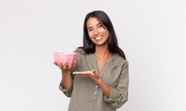 Jonge spaanse vrouw die vrolijk lacht, zich gelukkig voelt en een concept toont en een lege kom of pot vasthoudt