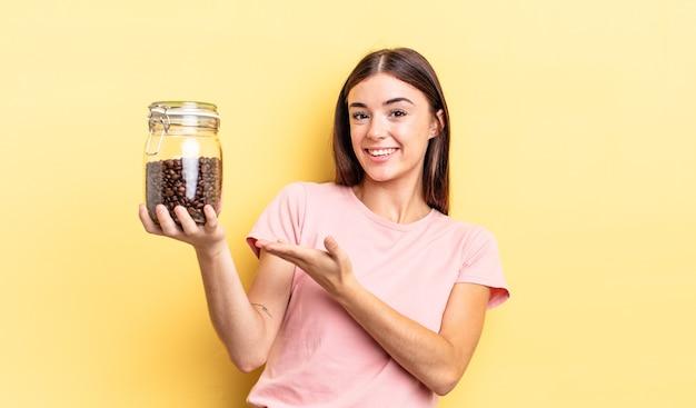 Jonge spaanse vrouw die vrolijk lacht, zich gelukkig voelt en een concept toont. koffiebonen concept