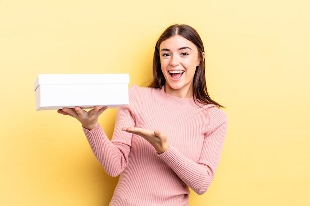 Jonge spaanse vrouw die vrolijk lacht, zich gelukkig voelt en een concept toont. lege doos concept