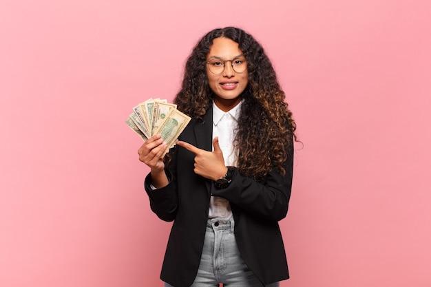 Jonge spaanse vrouw die vrolijk lacht, zich gelukkig voelt en naar de zijkant en naar boven wijst, een object in de kopieerruimte laat zien. dollar biljetten concept