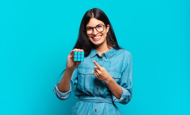 Jonge spaanse vrouw die vrolijk lacht, zich gelukkig voelt en naar de zijkant en naar boven wijst, een object in de kopieerruimte laat zien.
