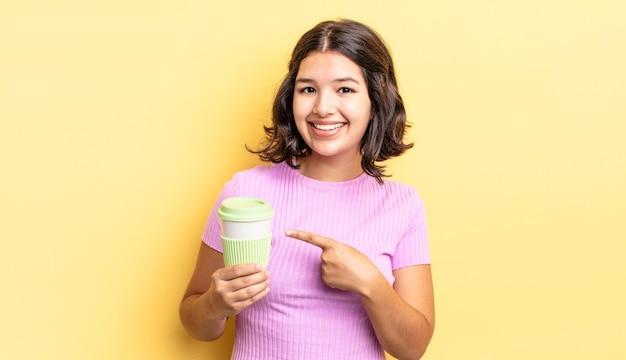 Jonge spaanse vrouw die vrolijk lacht, zich gelukkig voelt en naar de zijkant wijst. afhaal koffie concept