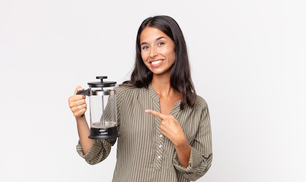 Jonge spaanse vrouw die vrolijk lacht, zich gelukkig voelt en naar de zijkant wijst en een handmatig koffiezetapparaat vasthoudt