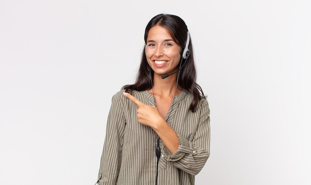 Jonge spaanse vrouw die vrolijk lacht, zich gelukkig voelt en naar de zijkant wijst met een headset. telemarketing concept