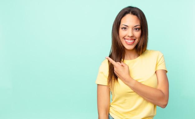 Jonge spaanse vrouw die vrolijk lacht, zich gelukkig voelt en naar de zijkant wijst