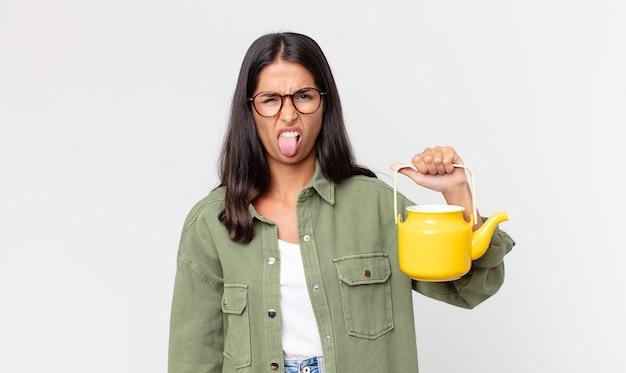 Jonge spaanse vrouw die walgt en geïrriteerd voelt en haar tong uitsteekt en een theepot vasthoudt