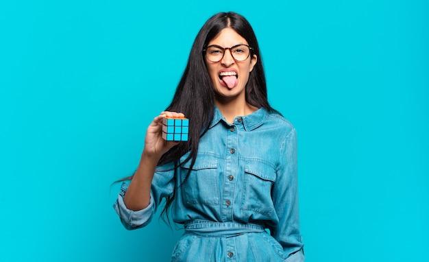 Jonge spaanse vrouw die walgt en geïrriteerd voelt, tong uitsteekt, een hekel heeft aan iets smerigs en vies. intelligentie probleem concept