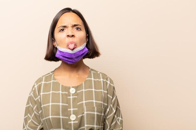 Jonge spaanse vrouw die walgt en geïrriteerd voelt, tong uitsteekt, een hekel heeft aan iets smerigs en vies