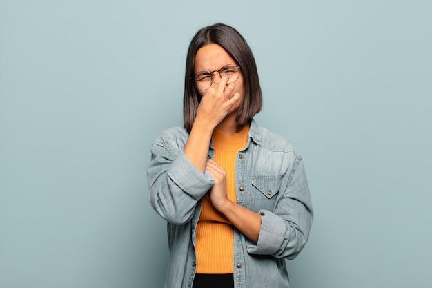 Jonge spaanse vrouw die walgt, neus vasthoudt om te voorkomen dat ze een vieze en onaangename stank ruikt