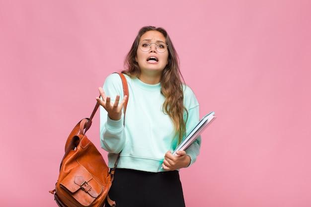 Jonge spaanse vrouw die wanhopig en gefrustreerd, gestrest, ongelukkig en geïrriteerd kijkt, schreeuwt en schreeuwt